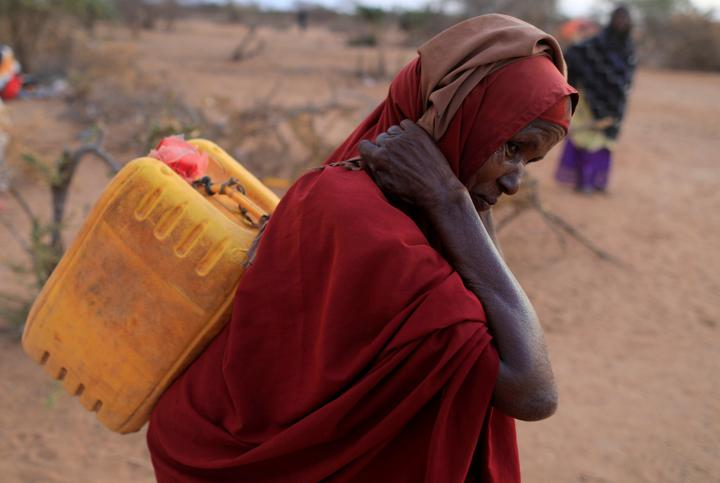 FILE PHOTO: An internally displaced woman from drought hit area carries a jerrycan of water as she walks towards her shelter at a makeshift settlement area in Dollow, Somalia April 4, 2017. REUTERS/Zohra Bensemra/File Photo