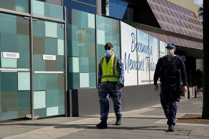 FILE PHOTO: Personnel from the Australian Defence Force and New South Wales Police Force patrol a street in the Bankstown suburb during an outbreak of the coronavirus disease (COVID-19) in Sydney, Australia, August 3, 2021. REUTERS/Loren Elliott/File Photo