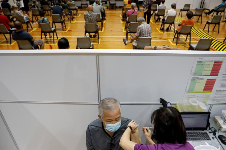 FILE PHOTO: A man receives his vaccination at a coronavirus disease (COVID-19) vaccination center in Singapore March 8, 2021. REUTERS/Edgar Su