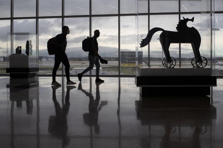 FILE PHOTO: Passengers walk past artwork between terminals at IAH George Bush Intercontinental Airport amid the coronavirus disease (COVID-19) outbreak in Houston, Texas, U.S., July 21, 2020. REUTERS/Adrees Latif
