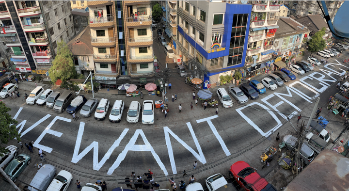 A slogan is written on a street as a protest after the coup in Yangon, Myanmar February 21, 2021 (Reuters)