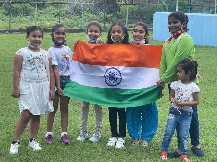 Children of the Indian diaspora in St. Kitts and Nevis hold the Indian flag as they prepare to hoist it to celebrate Indian Independence day.