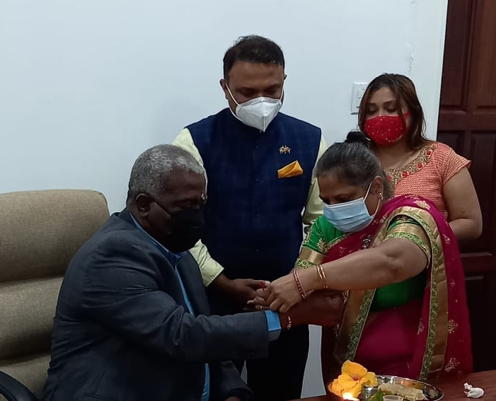 A female member of the Indian High Commission tying Rakhi on the wrist of the Prime Minister of the Cooperative Republic of Guyana, Mark Phillip, at the Prime Minister's office.