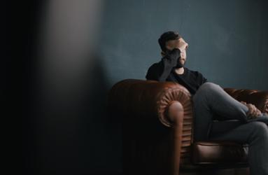 man sitting on sofa against wall
