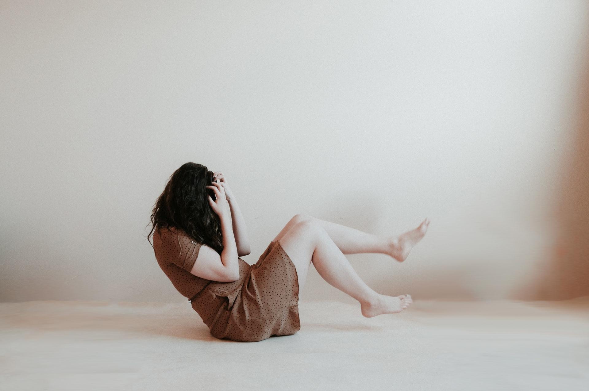 woman sitting on floor wearing brown dress