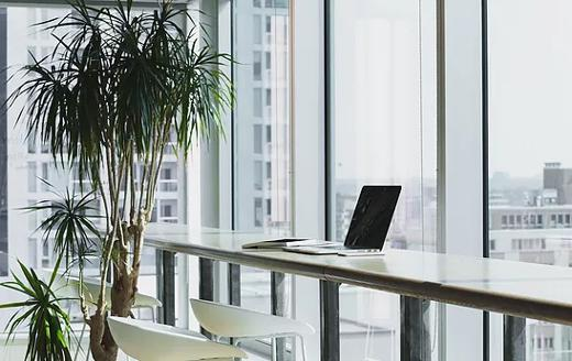 Desk with laptop on it overlooking an outside view