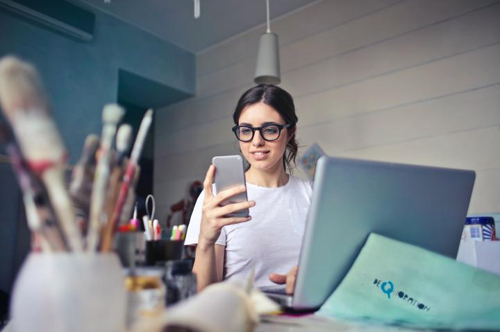 Person in art room looking at phone while also at desk with laptop