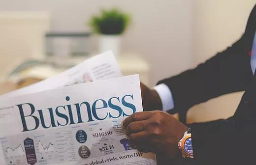 Person in suit reading a business newspaper