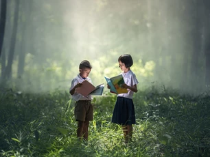 Two kids in the woods reading books