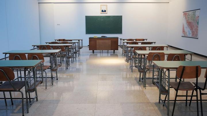 Empty school room with chalkboard and desks
