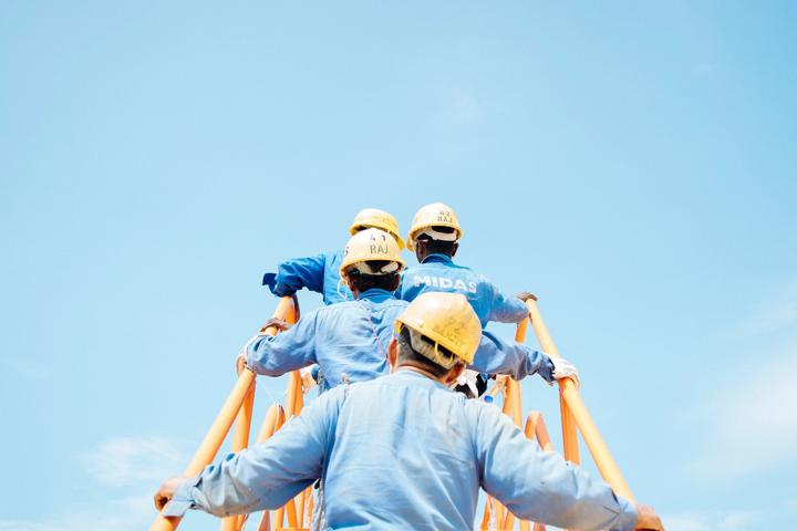 Four construction men walking up stairs