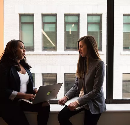 Two women sitting on window sill looking at laptop