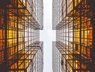 Photo looking straight up between two symmetrical buildings.