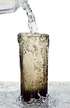 Water pouring into a glass cup overflowing.