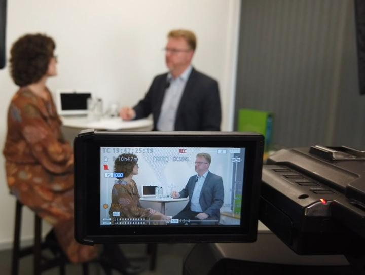 Video camera recording two people in interview meeting