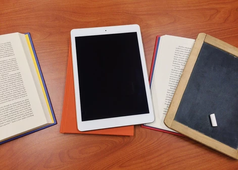 Books on table opened next to a tablet.