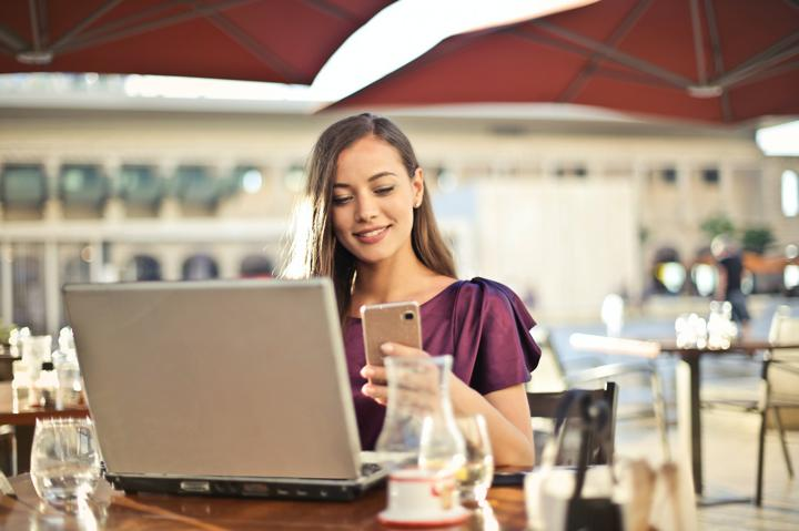 Person sitting at table on laptop looking at phone
