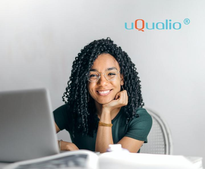 Person sitting at desk on computer smiling at camera