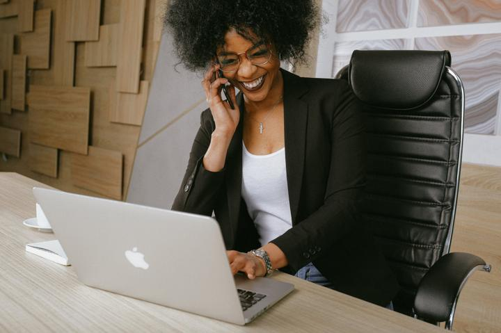 woman in black blazer on phone